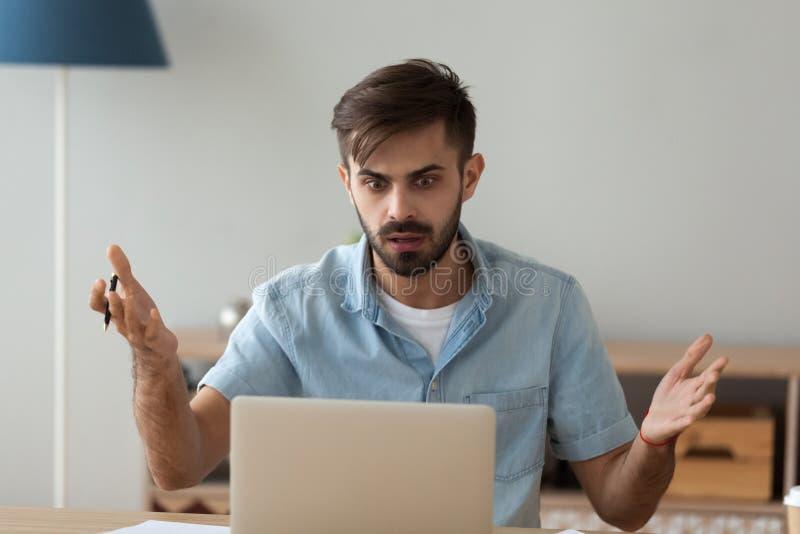 Trabajador de sexo masculino confundido chocado viendo el aviso en el ordenador portátil imagen de archivo