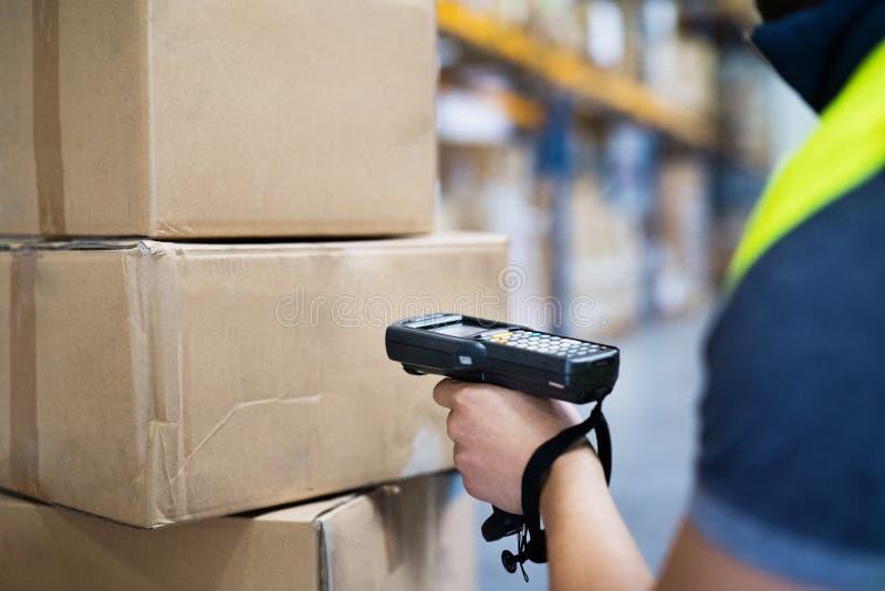 Trabajador de sexo masculino del almacén con el escáner del código de barras imágenes de archivo libres de regalías