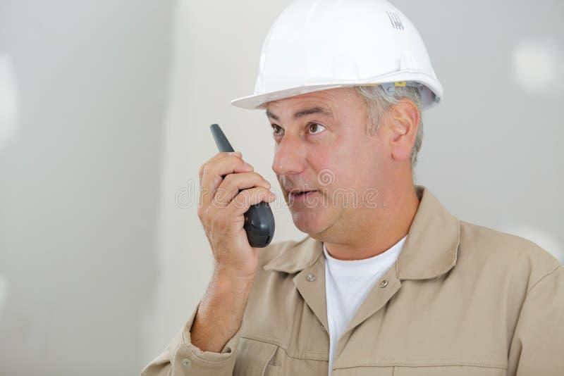 trabajador de sexo masculino en casco con el Walkietalkie en la acci?n de env?o foto de archivo