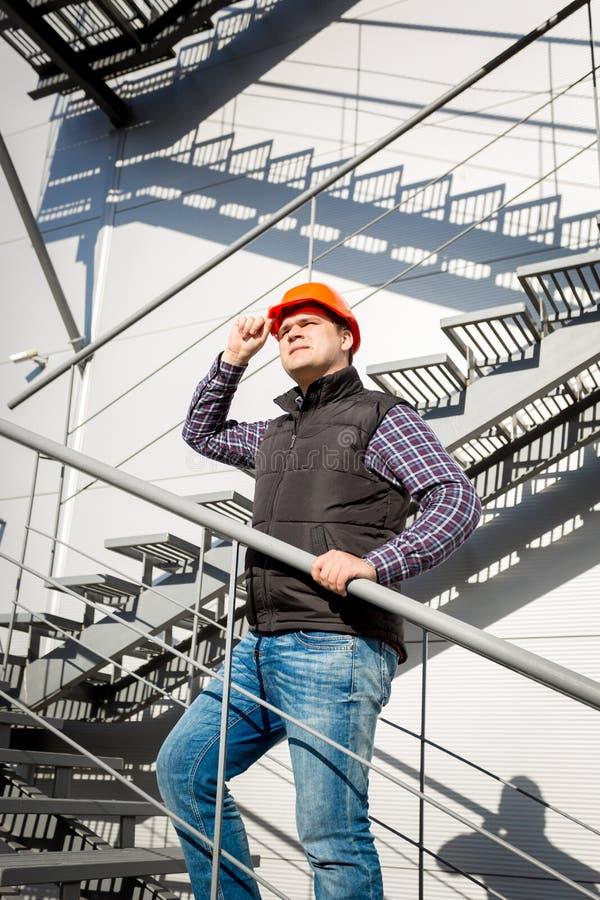 Trabajador de sexo masculino en el casco de protección que se coloca en la escalera de acero fotografía de archivo
