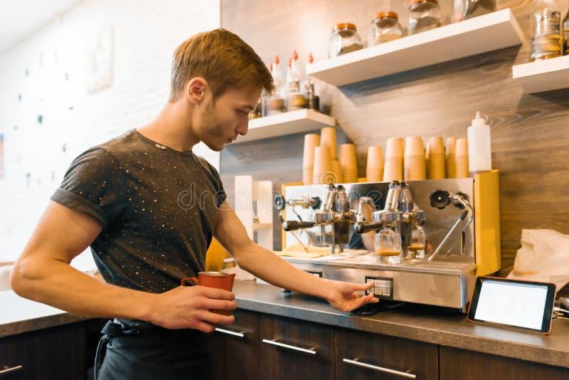 Trabajador de sexo masculino joven de la cafetería que hace el café con la máquina fotografía de archivo