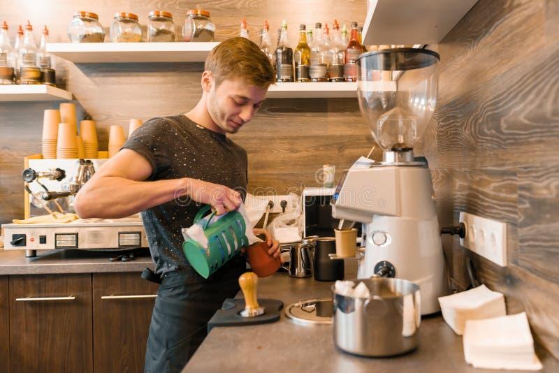 Trabajador de sexo masculino joven de la cafetería que hace el café con la máquina fotografía de archivo libre de regalías