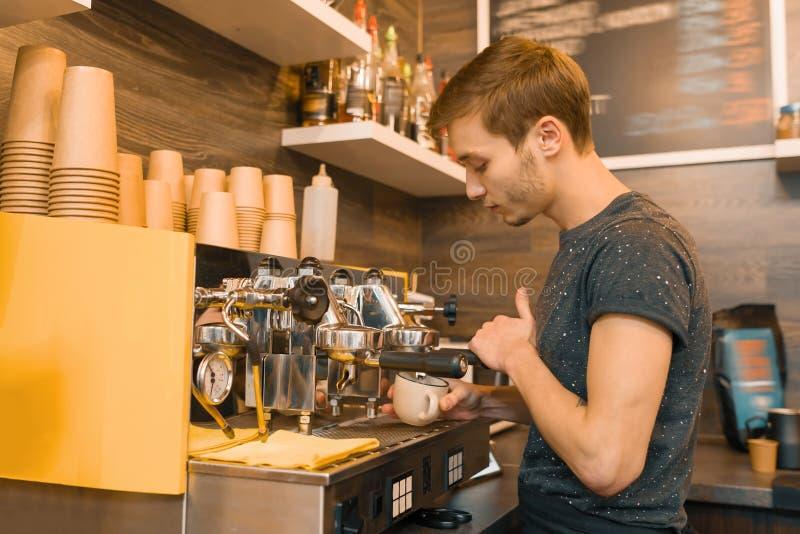 Trabajador de sexo masculino joven de la cafetería que hace el café con la máquina fotos de archivo