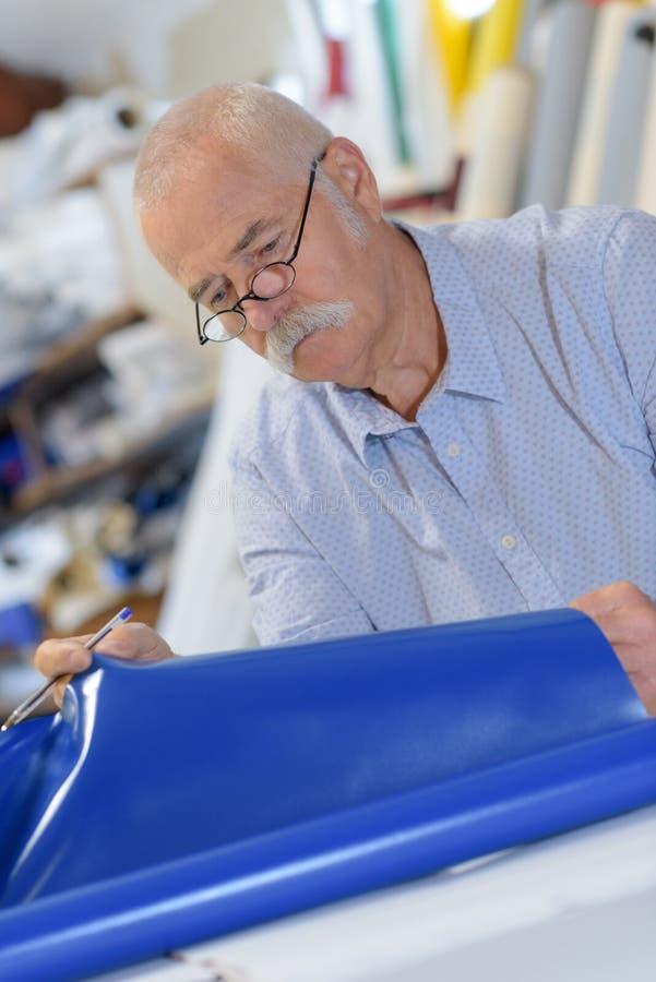 Trabajador de sexo masculino mayor que trabaja en industria de materias textiles imágenes de archivo libres de regalías