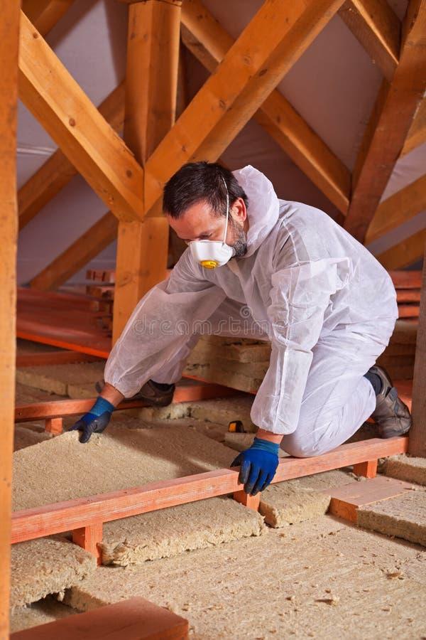 Trabajador de sexo masculino que coloca un panel aislador termal de las lanas de roca en medio fotos de archivo