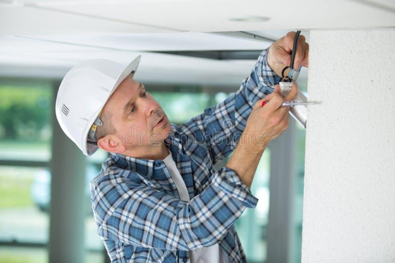 Trabajador de sexo masculino que hace el trabajo de mantenimiento sobre la cámara de seguridad fotos de archivo libres de regalías