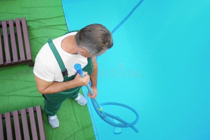 Trabajador de sexo masculino que limpia la piscina al aire libre con el submarino imagen de archivo libre de regalías