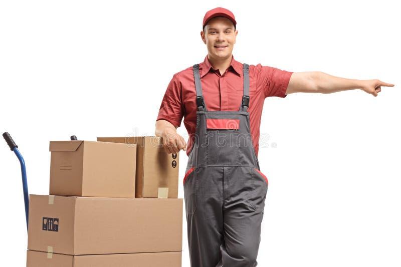 Trabajador de sexo masculino que se inclina en un camión de mano con una pila de cajas y de señalar foto de archivo libre de regalías