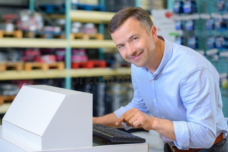 Trabajador de sexo masculino que usa el ordenador de la base de datos foto de archivo