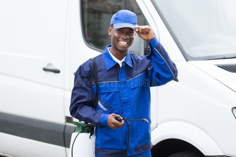Trabajador de sexo masculino sonriente joven con el rociador del pesticida imagen de archivo