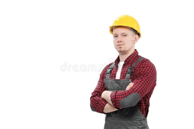 Trabajador de sexo masculino sonriente joven en un trabajador de construcción, en un casco amarillo, guardapolvos de trabajo y un fotografía de archivo