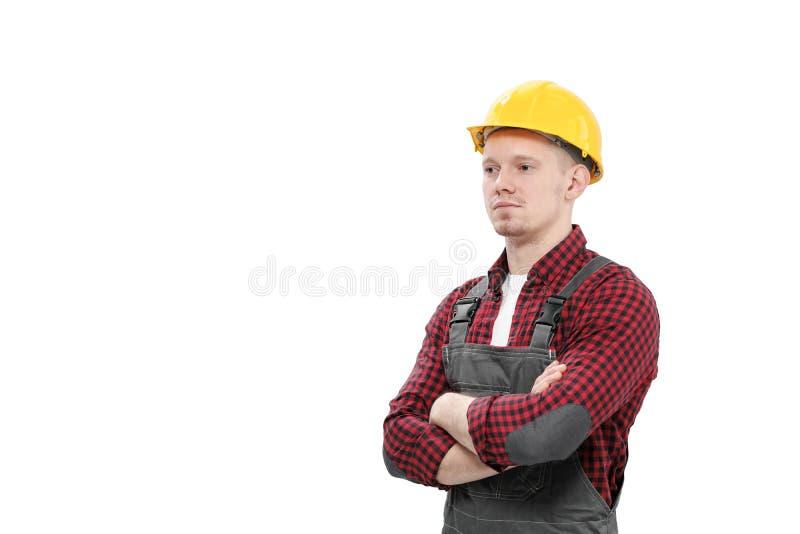 Trabajador de sexo masculino sonriente joven en un trabajador de construcción, en un casco amarillo, guardapolvos de trabajo y un imagenes de archivo