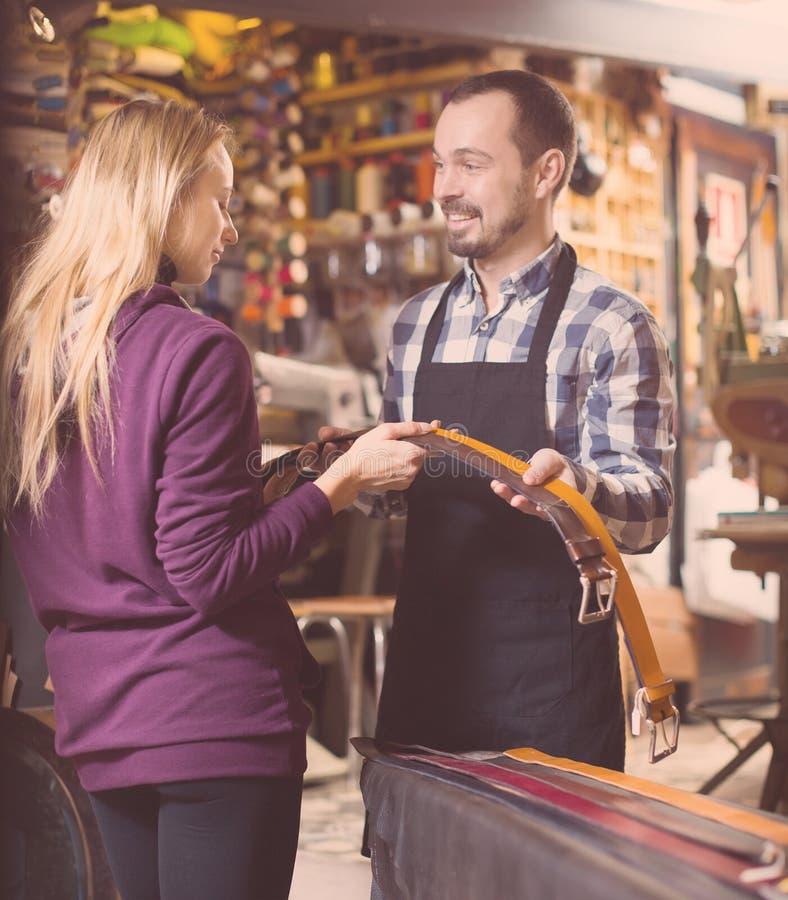 Trabajador de sexo masculino sonriente que ayuda al cliente femenino en elegir la correa fotografía de archivo libre de regalías