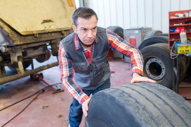 Trabajador de vulcanización que empuja el neumático pesado fotos de archivo libres de regalías