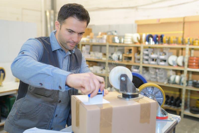 Trabajador de Warehouse que prepara el envío en almacén grande imagen de archivo libre de regalías