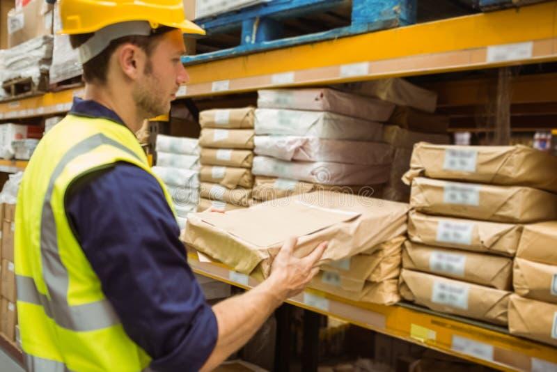 Trabajador de Warehouse que toma el paquete en el estante imágenes de archivo libres de regalías