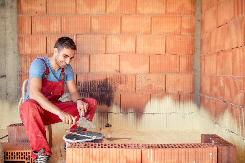 Trabajador del albañil de la construcción, paredes de ladrillo del edificio del albañil con la espátula y mortero fotografía de archivo