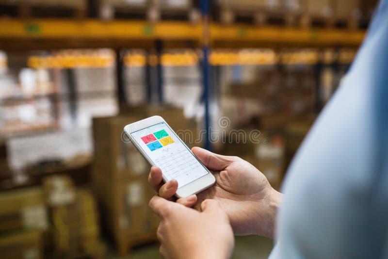 Trabajador del almacén del hombre con un smartphone fotografía de archivo libre de regalías
