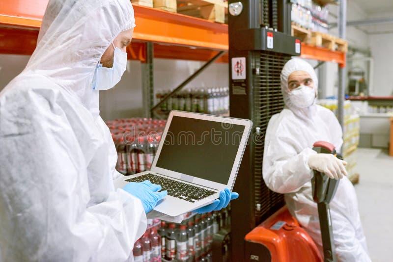 Trabajador del almacenamiento que usa el ordenador portátil fotos de archivo libres de regalías
