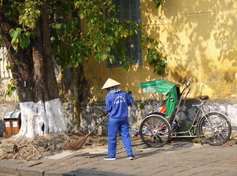 Trabajador del barrendero de camino con una escoba que limpia la calle en Hoi An imagen de archivo libre de regalías