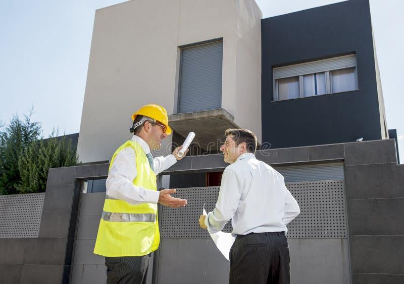 Trabajador del capataz del cliente y del constructor que habla en modelos de la construcción de nueva viviendas en concepto del n fotografía de archivo libre de regalías