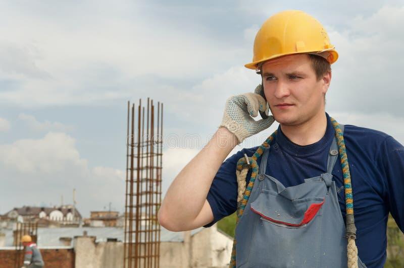 Trabajador del constructor con el teléfono móvil foto de archivo libre de regalías