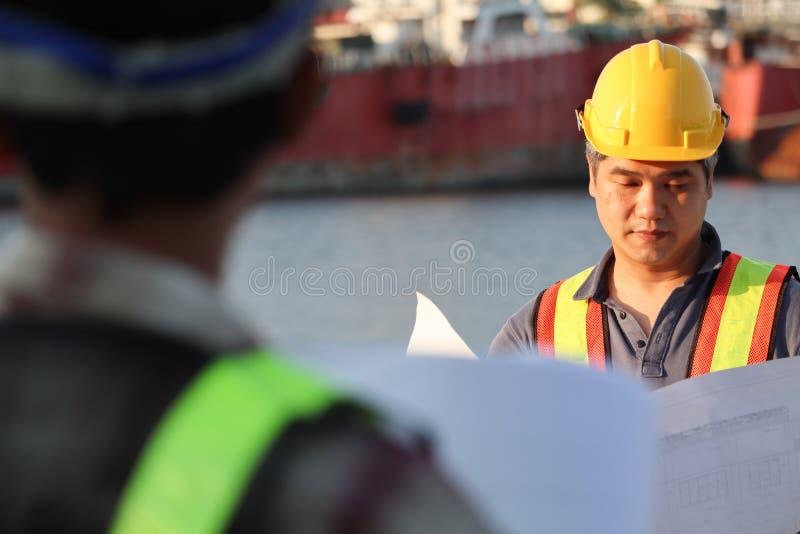 Trabajador del constructor en uniforme con el cinturón de seguridad en el emplazamiento de la obra imágenes de archivo libres de regalías