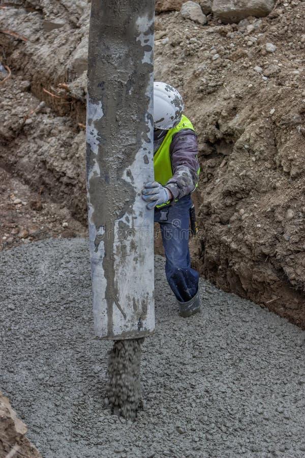 Trabajador del constructor que apunta y que coloca el hormigón 2 foto de archivo