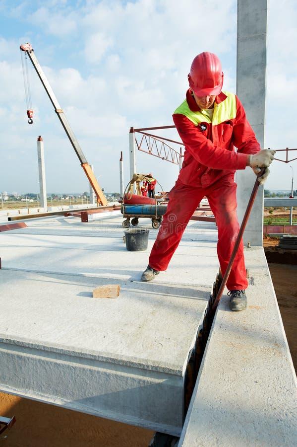Trabajador del constructor que instala el bloque de cemento imagen de archivo