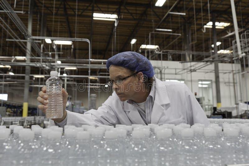 Trabajador del control de calidad que comprueba el agua embotellada en la planta de embotellamiento imagen de archivo libre de regalías