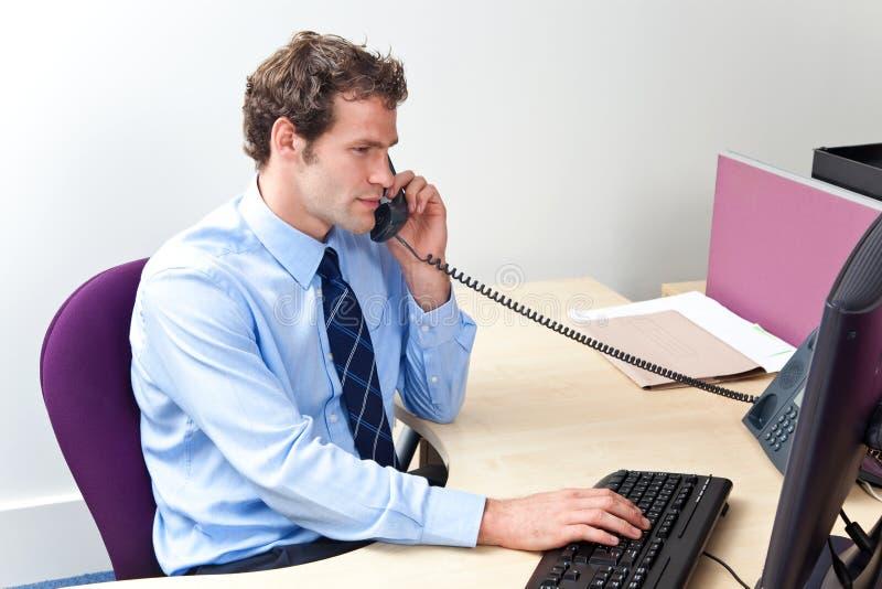 Trabajador del cuidado del cliente en una oficina en el teléfono fotografía de archivo