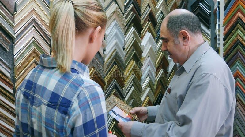 Trabajador del hombre mayor que ayuda al cliente femenino joven a coger el marco para una imagen en taller foto de archivo