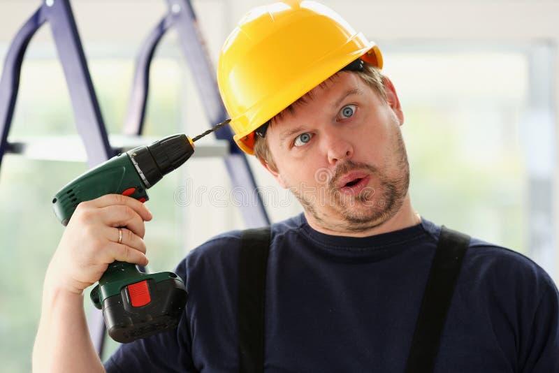 Trabajador del idiota que usa el retrato del taladro eléctrico imagen de archivo libre de regalías