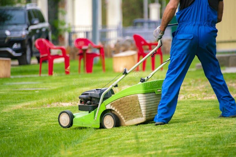 trabajador del jardinero que corta la hierba con el cortacéspedes en los campos del césped del patio trasero fotos de archivo