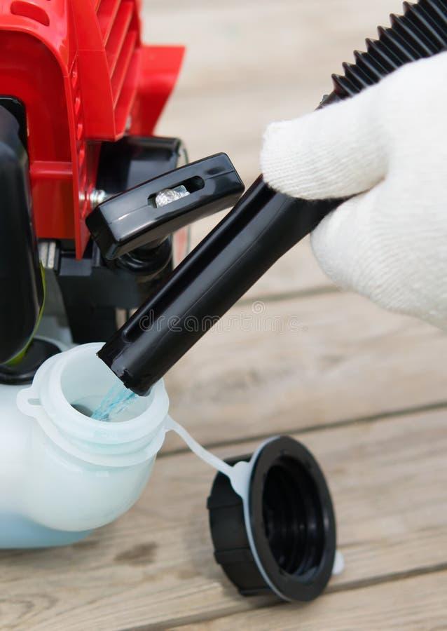 trabajador del mantenimiento del césped, motosierra azul del combustible de los repuestos, en un fondo de madera imagen de archivo