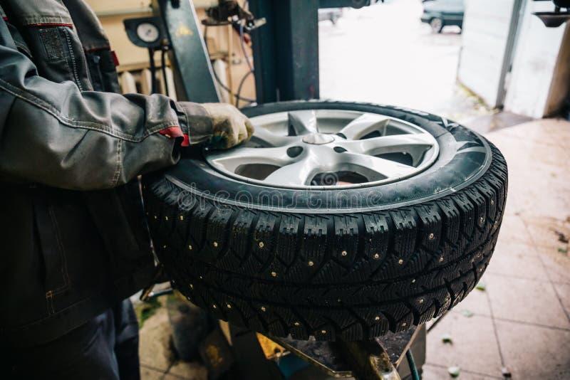 Trabajador del mecánico de coche que hace el reemplazo y la rueda del neumático que equilibran con el equipo especial en la gasol imagenes de archivo