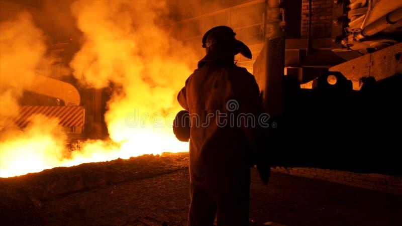 Trabajador del metalúrgico en uniforme protector en la planta siderúrgica que controla proceso de colada caliente del metal fundi imágenes de archivo libres de regalías