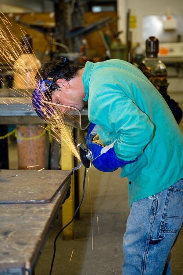 Trabajador del metal que usa la amoladora fotografía de archivo