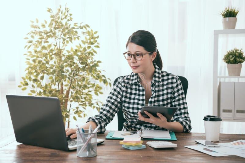 Trabajador del negocio de la muchacha que sostiene la tableta digital móvil foto de archivo