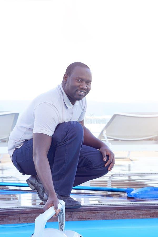 Trabajador del personal del hotel que limpia la piscina fotos de archivo libres de regalías