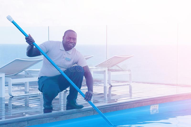 Trabajador del personal del hotel que limpia la piscina mantenimiento fotos de archivo libres de regalías