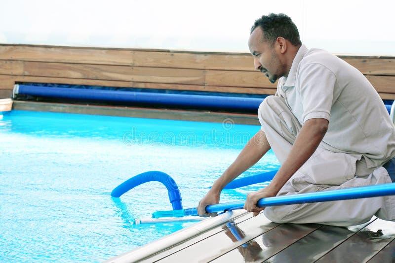 Trabajador del personal del hotel que limpia la piscina mantenimiento imagenes de archivo