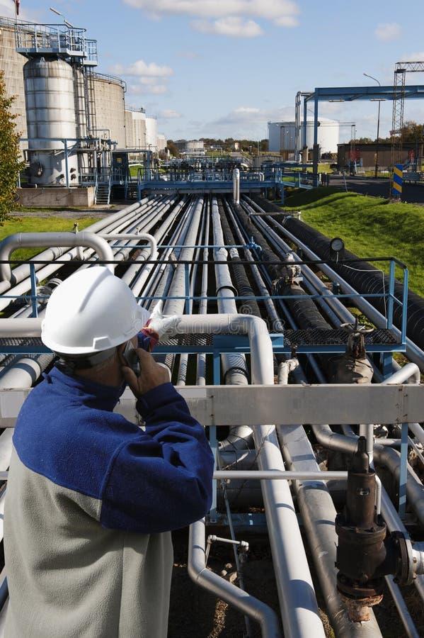 Trabajador del petróleo y gas delante de la refinería fotos de archivo
