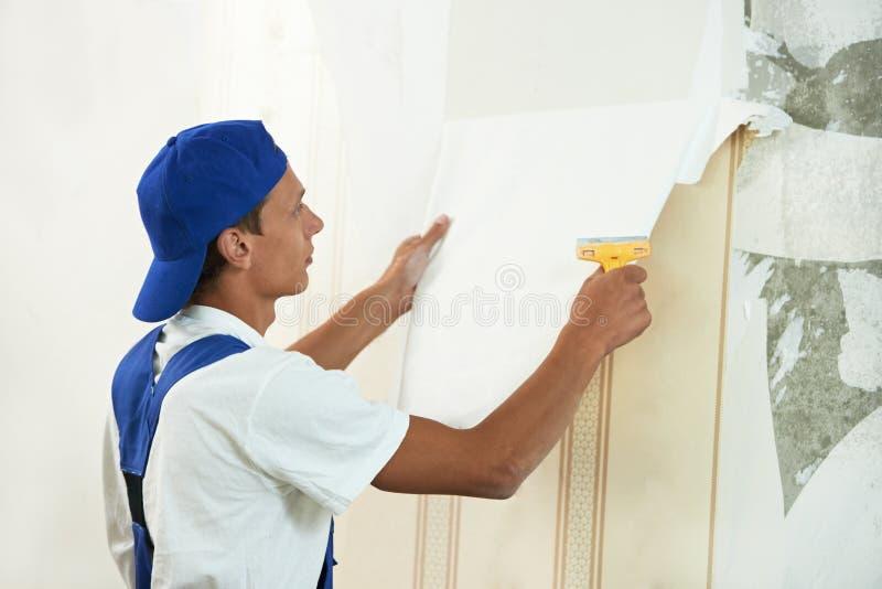Trabajador del pintor que pela apagado el papel pintado imagenes de archivo