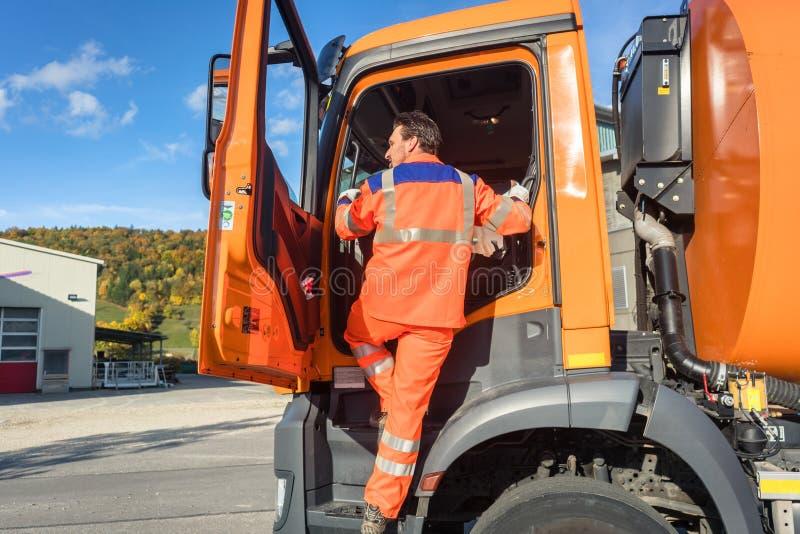 Trabajador del retiro de la basura que consigue en el vehículo de la disposición fotos de archivo