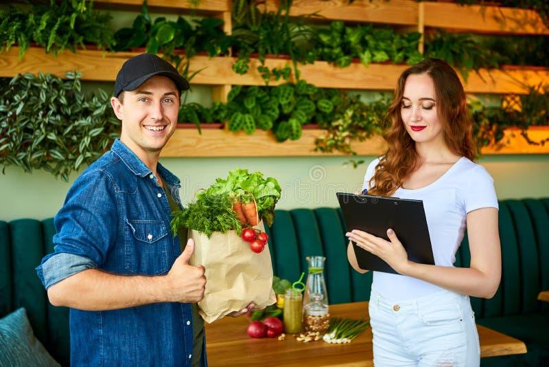 Trabajador del servicio de mensajero que entrega la comida fresca a un cliente feliz de la mujer que firma algunos documentos en  foto de archivo