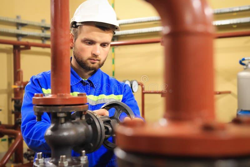 Trabajador del técnico en sistema de calefacción El operador de la estación abre la válvula del agua en tubería El hombre trabaja fotografía de archivo