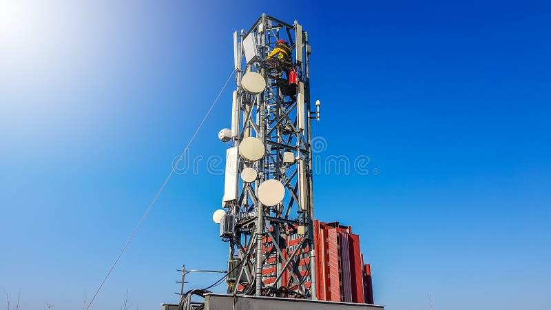 Trabajador del técnico que sube en un palo de la red de radio del teléfono que instala la nueva antena foto de archivo