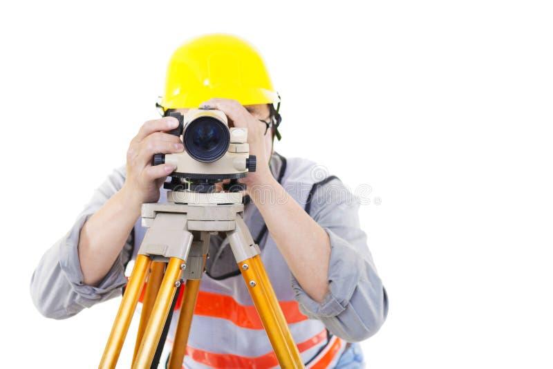 Trabajador del topógrafo que hace la medida y aislado fotos de archivo