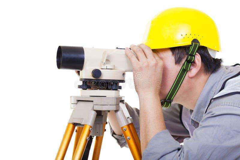 Trabajador del topógrafo que hace la medida y aislado imagen de archivo